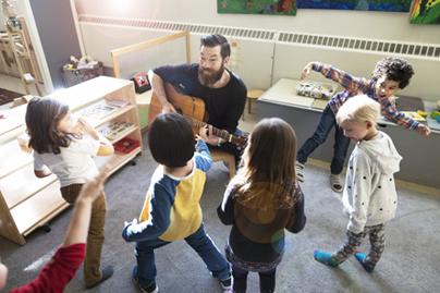Man playing guitar for dancing children